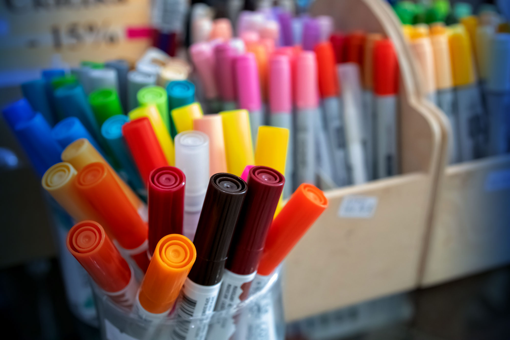 A large selection of coloured textas and sharpies in boxes and jars